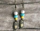 pearl. a pair of freshwater pearl owl charm earrings.