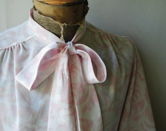 Classy vintage 80s white silky polyester secretary blouse wth pastel pink abstract print and tie -bow. Made by Shapely. Size 12.