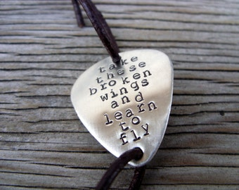Hand stamped nickel silver guitar pick bracelet take these broken wings with black leather cord-  adjustable