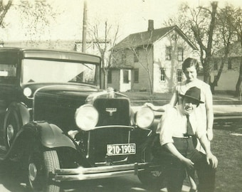Big Man Sitting on Car Front Bumper With Daughter Vintage Black and White Vintage Photo Photograph
