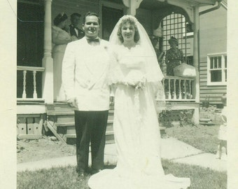 Wedding Day 1940s Bride and Groom Standing on Front Yard of House in Town Vintage Black and White Photo Photograph