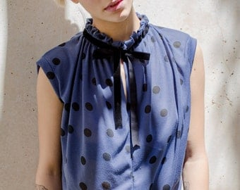 under 50, blue polka dots shirt with black velvet tying and pleats