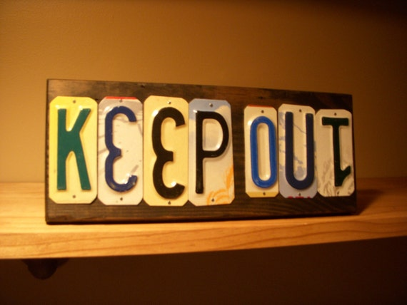Bright and whimzical KEEP OUT sign made with recycled license plates.