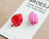 Two vintage leaf brooches plastic pink red
