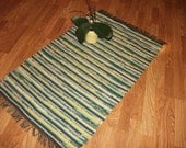 Hand-woven, rag rug made of recycled materials in shades of green, yellows, and peach.