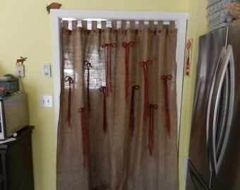 button tab burlap drapes with red fringed burlap bows and red buttons.