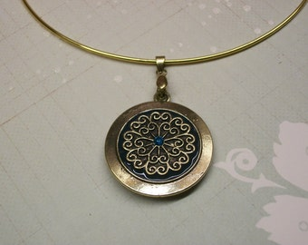 Gold choker with gold and blue circular pendant.