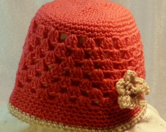 Pink crocheted cloche hat with applied flower detail