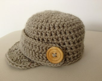 Boys newsboy cap with peak and button detail. Fawn cap with wooden button detail. Other colours available.