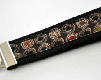 Modern Earth Toned Circled Fabric on a Dark Brown Background Fabric Wristlet Keychain with Black Heavy Duty Cotton Webbing