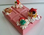 Small plastic case container decorated by delicious looking clay food - Block strawberry chocolate