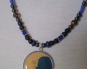 Blue/Black Necklace with Crescent Man in the Moon Pendant