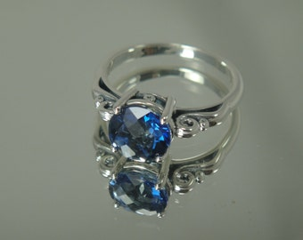 Sterling silver scroll ring with a synthetic checker board sapphire.