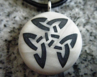 Trinity Celtic Knot hand carved on a polymer clay mother of pearl color background.  Pendant comes with a FREE 3mm necklace.