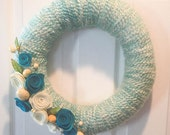 SPRING YARN WREATH with roses and speckled eggs.