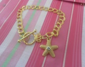 COACH Starfish Charm on Gold Plated Charm Bracelet.