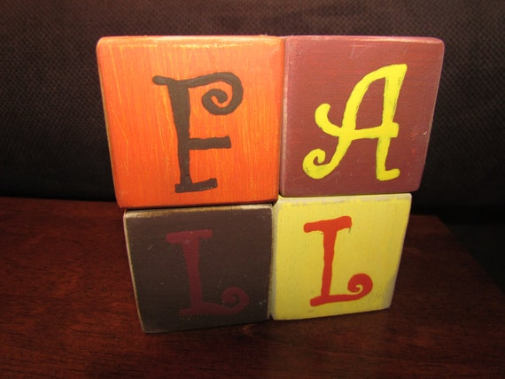 Four wooden blocks that spell out fall in fall colors