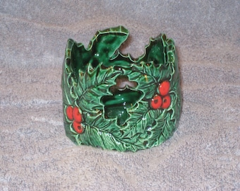 Ceramic,  votive candle holder  with holly leaves and red berries as the design. Hand painted by Joan Davis