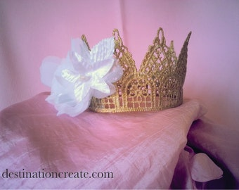 Charming baby or child crown handcrafted from gold lace and embellished with a white flower.