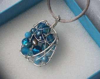 Blue Apple necklace combining glass and semi precious beads wrapped in a silver plaited wire cage hanging from an elegant grey silk cord.