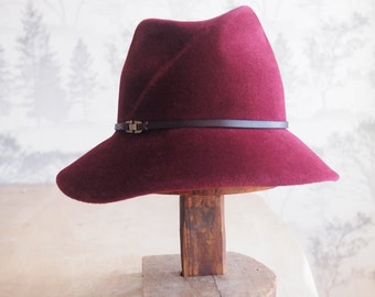 Camille:  Burgundy velour felt asymmetrical fedora with hand dyed burgundy leather trim and antique brass finding.