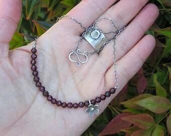 garnet gemstone and karen hill tribe fine silver necklace. january birthstone necklace. dainty flower charm necklace.