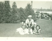 1920s Happy Family Laying in the Grass Posing for Picture Cars City in Background Vintage Black And White Photo Photograph