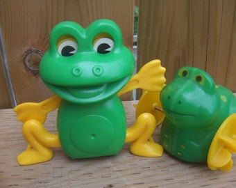 Two Vintage Cool Hard Plastic Frogs. One walks sideways and moves arms and eyes, the other rolls.