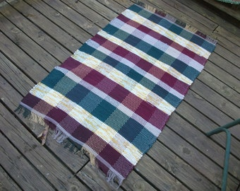 Hand-woven, rag rug made of recycled sheets, and sewing scrapes in dark green, gold, tan, and maroon.