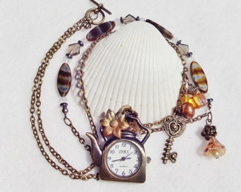 Teapot pocket watch, watch pendant teapot, with brown and amber tone beading and charms..