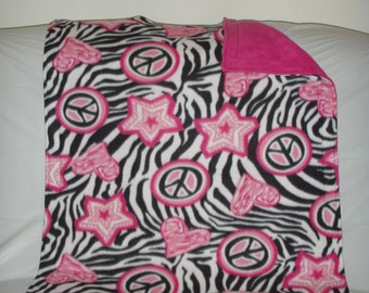 Pet Blanket - bright pink hearts, stars and peace sign on a black and white zebra background with reversible solid bright pink fleece
