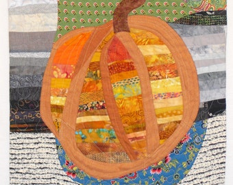 Fiber Art Wall Hanging,fabric collage, orange pieced pumpkin on a French blue plate,black,grey,green, and white pieced fabric background.