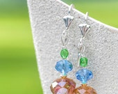 Handmade earrings, designed and made from blue, yellow and orange crystals.