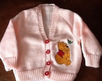 Peach hand knitted baby cardigan with Winnie the Pooh embroidery