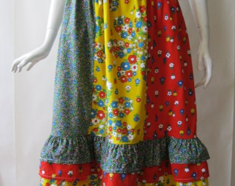 1970's paneled ruffle skirt, in red, yellow, and multicolor flower prints, with ruffled hem, small / medium