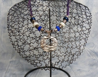 Necklace: Purple Ribbon Necklace with Black and White Zebra Striped Pendant and White, Blue, and Silver Accent Beads