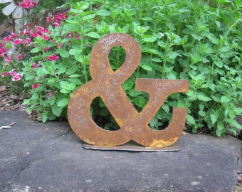 "Metal ampersand ""&"" on stand"