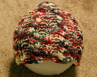 Child's red, green, and white cabled hat