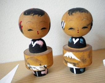 Vintage wooden kokeshi doll bobblehead pair with Mt Fuji scenes