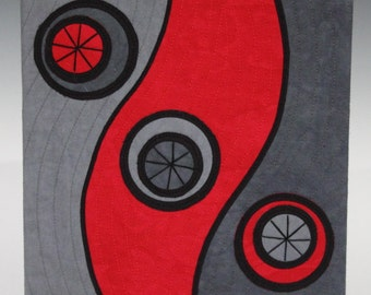 Circles and waves fiber art in shades of gray and a touch of red