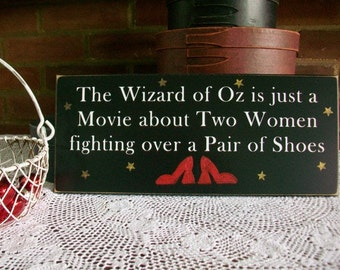 The Wizard Of Oz Two Women Fighting Over a Pair of Shoes Wood Sign Wall Decor