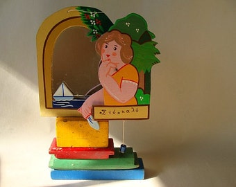 vintage handmade souvenir mirror from greece with a girl who has a moveable waving arm