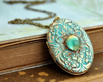 vintage brass floral locket, green patina, ENCHANTED, vintage 70s brass locket necklace with vintage two tone blue glass cab Victorian
