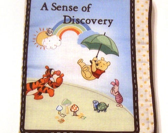 A Sense of Discovery Soft Cloth  Book using Pooh Bear fabrics in bright bold colors and piping around the edges