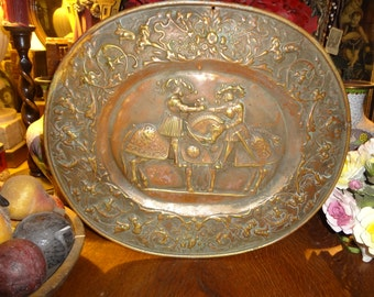 Gorgeous German  brass repousse with deep reds and green under tones plaque of jousters