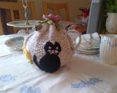 A hand knitted washable tea cosy in a cat and mouse design