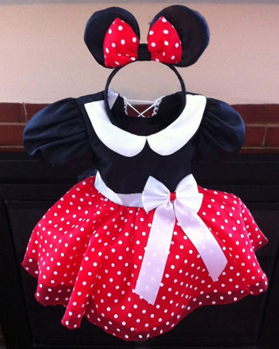 Dress up baby in this adorable Minnie Mouse costume featuring white polka dots printed on red puff sleeves and a multilayered skirt. The center of the Peter Pan collar is accented with a small Minnie Mouse .