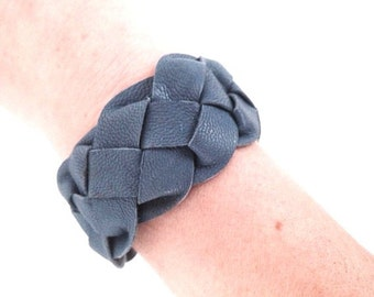Blue leather cuff. Plaited leather  bracelet with silver colored metal lobster claw clasp.