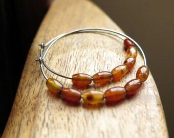 carnelian earrings. hypoallergenic hoops. dark silver hoop earings in niobium wire.