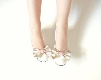 Bow shoe clips in gold and pink leather . Anita